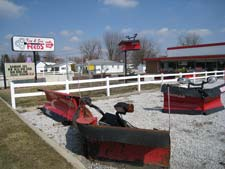 Outside sign, store and snowplows